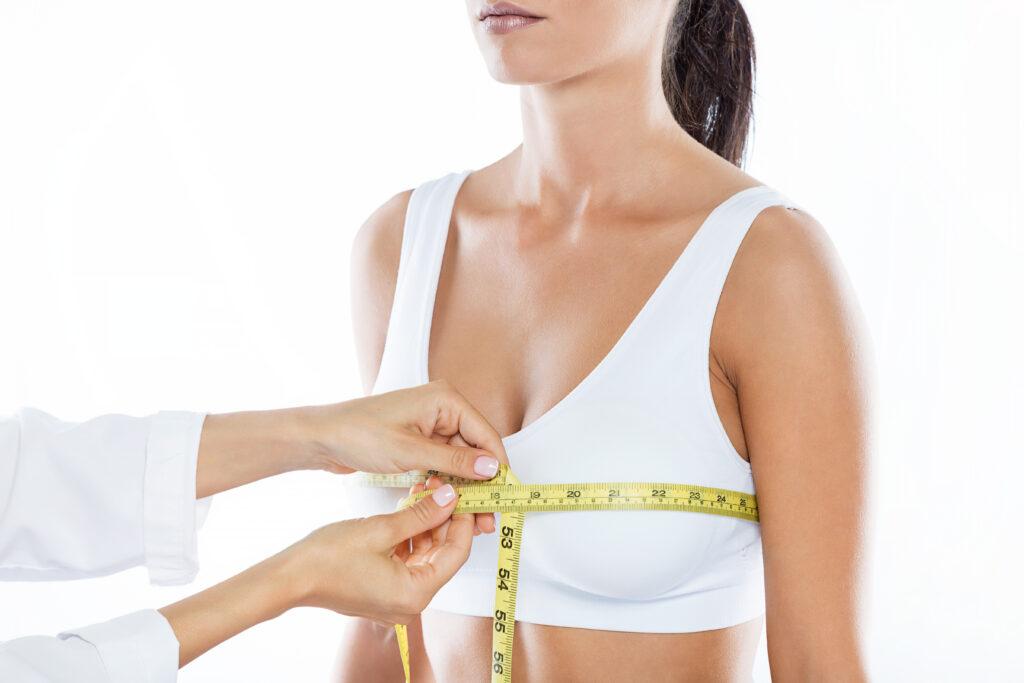 Médico com um fita métrica medindo um dos seios de uma mulher que pretende fazer uma mamoplastia redutora