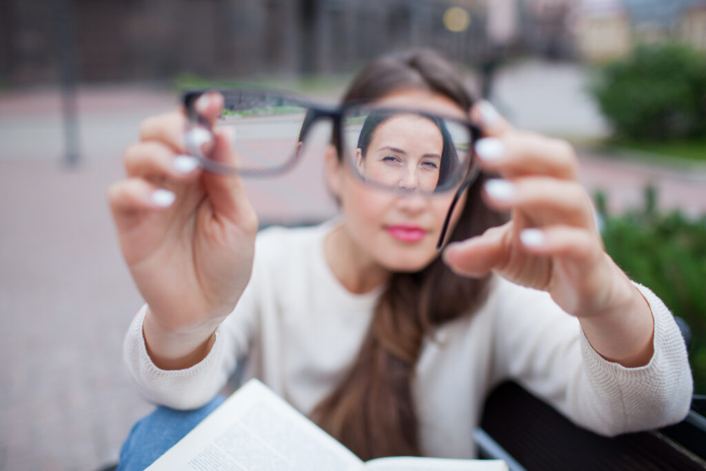 Mulher desfocada com os braços esticados segurando um óculos que está em foco no primeiro plano