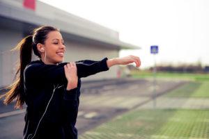 Mulher sorridente se alongando para combater a fibromialgia