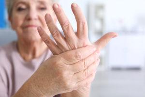 Mulher idosa segurando sua mão que está doendo por causa de lesões nos ossos, a síndrome do túnel do carpo