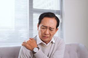 Senhor idoso com a mão no ombro e uma expressão de dor, ele está com dor no ombro