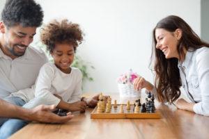 Família feliz jogando xadrez para cultivar a saúde emocional infantil