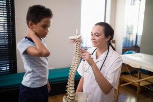 Garoto com a mão no pescoço indicando torcicolo olhando para um médica que está com um modelo de uma coluna apontando para as vertebras da região do pescoço