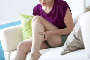 Moça sentada em um sofá com as mãos na panturrilha mostrando que está com dor nessa área proveniente de uma Trombose venosa profunda