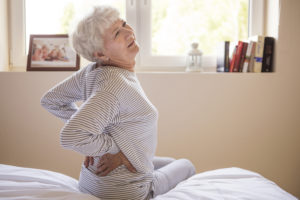 Mulher idosa sentada em sua cama com as mãos nas costas e uma expressão de dor