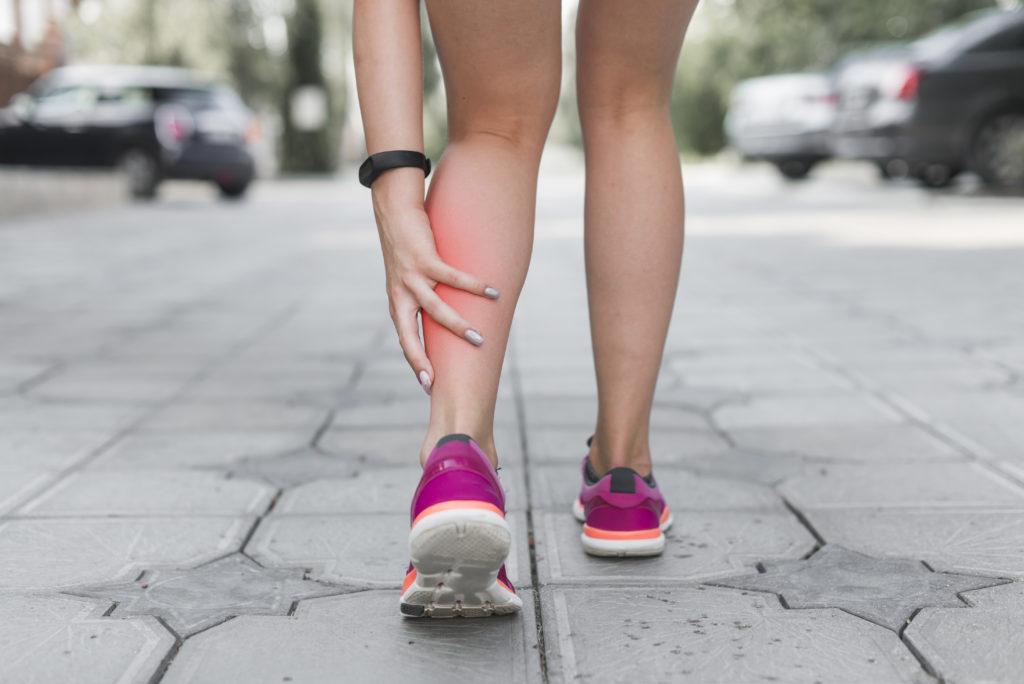 close por trás das pernas de uma mulher com ela segurando a panturrilha esquerda e a região está avermelhada por causa da dor proveniente da má circulação