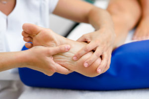 Close de um pé recebendo massagem para tratar dos efeitos do pé diabético