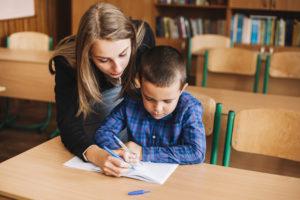 Professora ensinando criança com distúrbios de aprendizagem em uma sala de aula com mesas e cadeiras de madeira