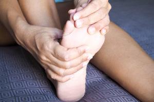close de mãos mexendo nos dedos e na sola do pé que estão doendo por causa da gota