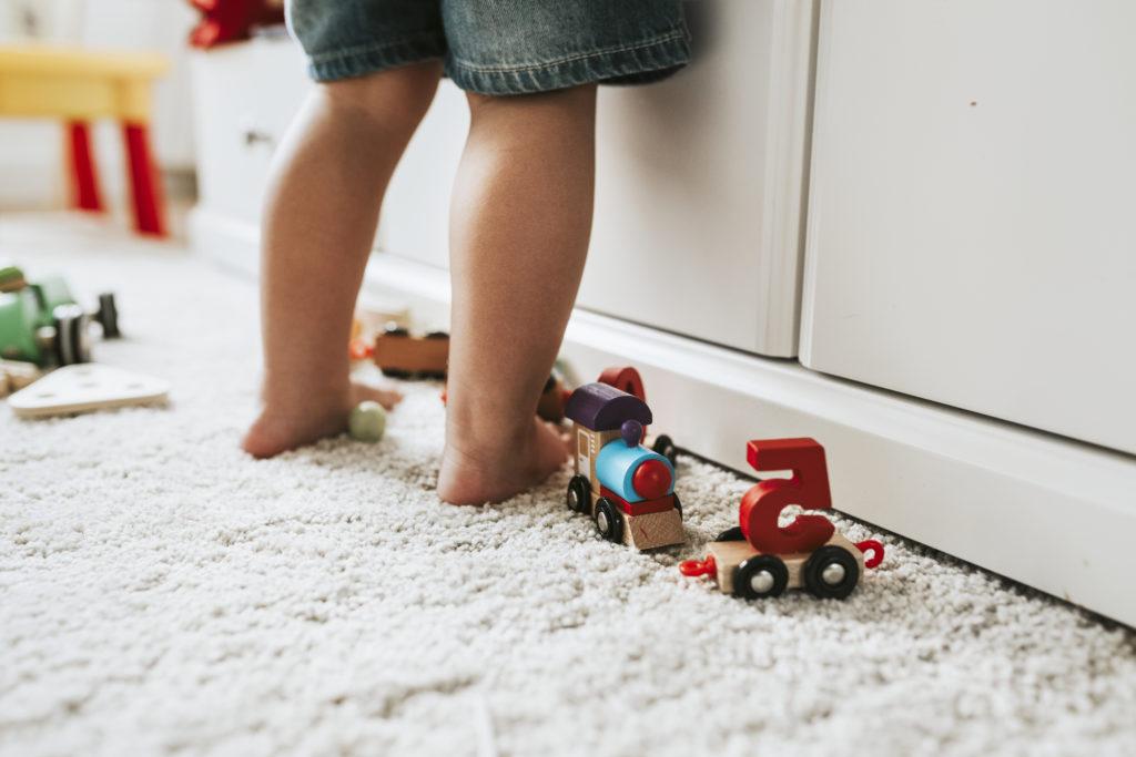Close de pernas de criança em pé brincando no quarto