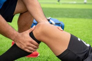 Jogador de futebol dentro do campo tendo o joelho examinado por um fisioterapeuta por causa de uma lesão que sofreu durante uma partida. Existe a possibilidade de ser ruptura do menisco.