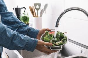 Homem lavando verduras na pia da cozinha para prevenir da toxoplasmose