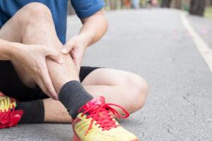 Homem com roupa de corrida sentado no asfalto com as mãos na canela indicando dores na região proveniente da canelite