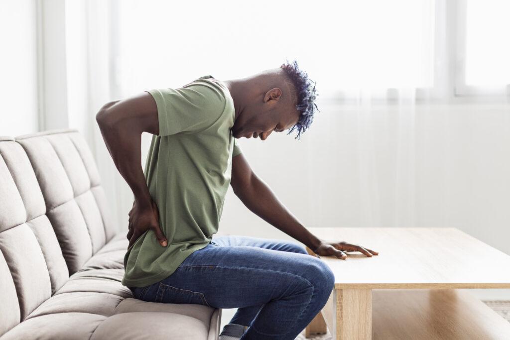 Homem sentado no sofá com uma das mõas na parte inferior das costas, a cabeça abaixada e a outra mão apoiada na mesa. Ele está com dor ciática