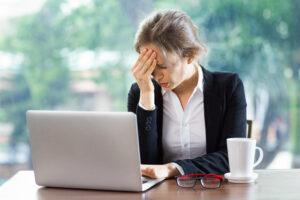 Mulher no trabalho sentada na mesa em frente ao notebook com a mão na testa por causa de enxaqueca