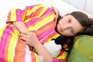Garota com dor de barriga, um dos sintomas das parasitoses intestinais, deitada na cama