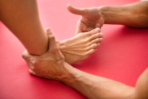 Close de um tendo a área com joanete tocada por outra mão em cima de uma tatame vermelho