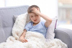 Menino no sofá de casa com dor de cabeça proveniente de meningite