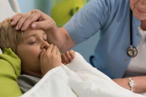 Garoto embaixo das cobertas tossindo o que indica pneumonia infantil. Uma médica passa a mão na cabeça do menino.