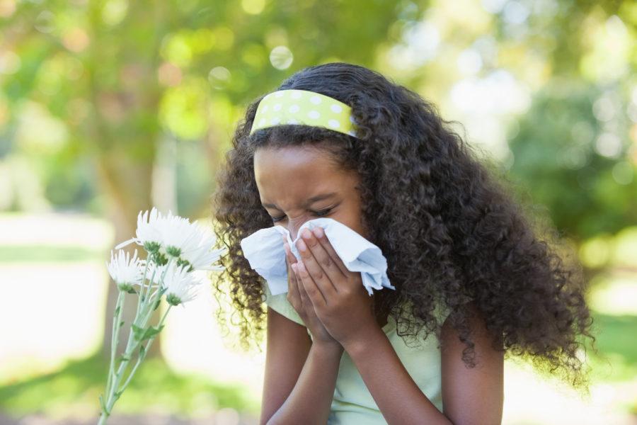 Garota com resfriado espirrando em um lenço