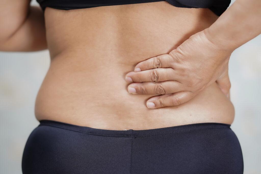 Close de mulher com obesidade de costas com as mãos na lombar indicando que ela está com problemas na coluna