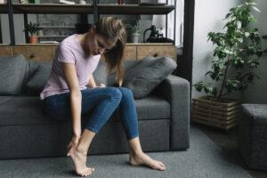 Mulher, sentada em um sofá, mexendo no calcanhar por estar com dor proveniente de uma fascite plantar