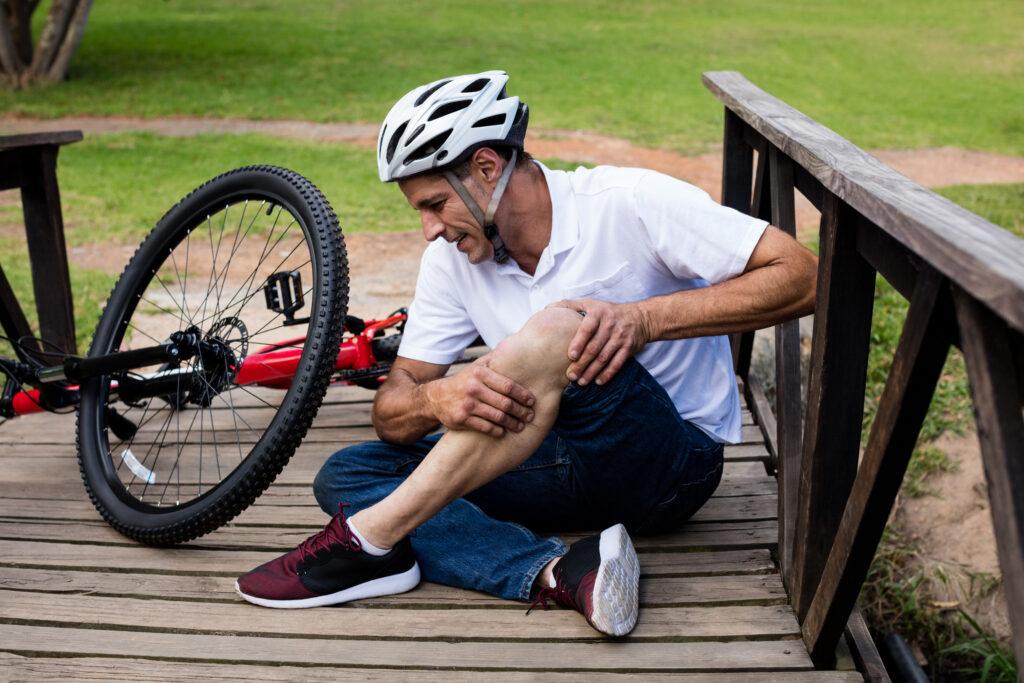 Homem mais velho sentado no chão de uma ponte com as mãos no joelho por causa de uma lesão provocada pelo ciclismo. Ele está de capacete e a bicicleta está logo atrás dele.