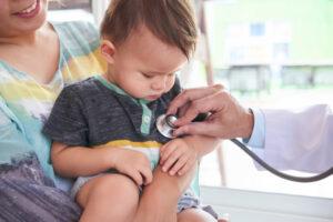 Criança no colo da mãe sendo auscultada para ver se tem bronquiolite