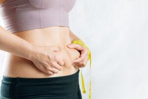Mulher apertando a gordura da barriga para indicar que precisa de fazer lipoaspiração. elas tem uma fita métrica em uma das mãos.