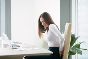 Em um escritório, mulher com hemorroida sentada com dor na região do ânus