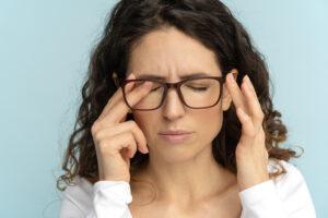 Mulher de óculos coçando um dos olhos por estar com um dos incômodos nos olhos.
